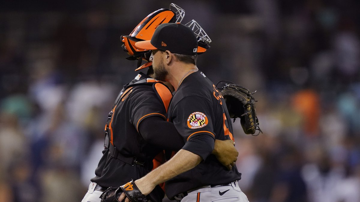 Baltimore Orioles relief pitcher Cole Sulser hugs catcher Pedro Severino after the team' 4-3...