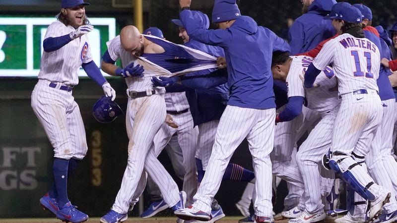 The Chicago Cubs celebrate David Bote's game winning RBI single as they tear off his jersey...