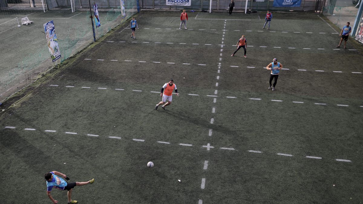 en play soccer at a local club, Play Futbol 5, in Pergamino, Argentina, Wednesday, July 1, 2020. In order to continue playing amid government restrictions to curb the spread of the new coronavirus, the club divided its soccer field into 12 rectangles to mark limited areas for each player, keeping them from making physical contact. (AP Photo/Natacha Pisarenko)