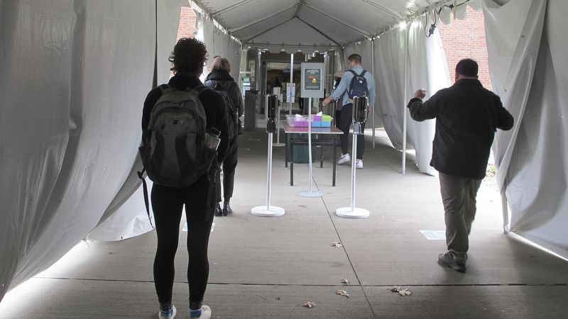 In this Nov. 12, 2020, photo, University of Vermont students walk through a tent leading to a...