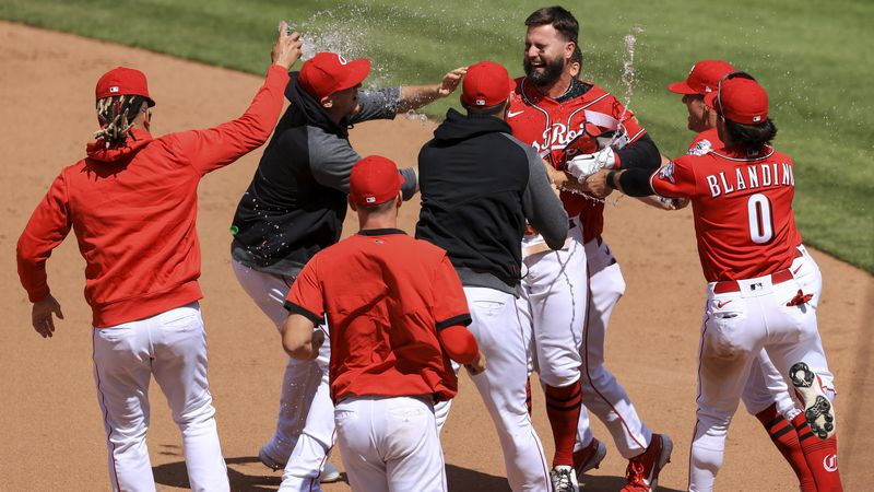 Cincinnati Reds' Jesse Winker, back right, celebrates with teammates after hitting an RBI...