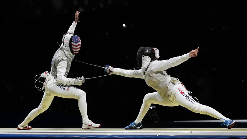 Lee Kiefer of the United States,m left, and Rio Azuma of Japan compete in the women's Foil team...