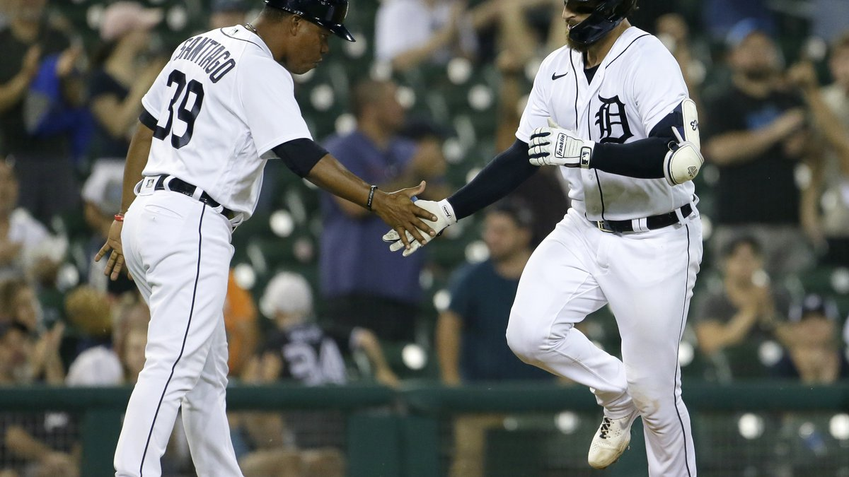 Detroit Tigers' Eric Haase, right, is congratulated by third base coach Ramon Santiago after...