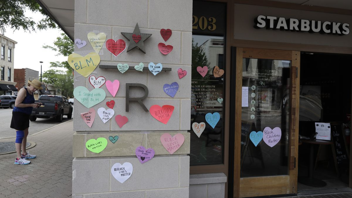 """In this Thursday, June 4, 2020 file photo, a woman looks at the plywood covering the windows of a Starbucks store in downtown Naperville, Ill., as Naperville residents used hearts to post messages in support of the Black Lives Matter movement. Starbucks is the latest company to say it will pause social-media ads after a campaign led by civil-rights organizations called for an ad boycott of Facebook, saying it doesn't do enough to stop racist and violent content. Starbucks said Sunday, June 28 that its actions were not part of the """"#StopHateforProfit"""" campaign, but that it is pausing its social ads while talking with civil rights organizations and its media partners about how to stop hate speech online.(AP Photo/Nam Y. Huh)"""