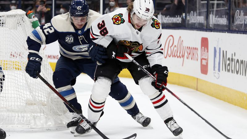 Columbus Blue Jackets forward Alexandre Texier, left, reaches for the puck against Chicago...