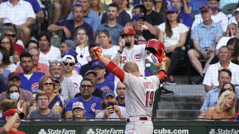Cincinnati Reds' Joey Votto gestures while returning to the dugout after hitting a home run...