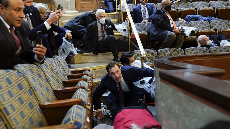 People shelter in the House gallery as protesters try to break into the House Chamber at the...