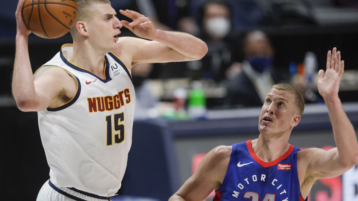 Denver Nuggets center Nikola Jokic (15) passes around Detroit Pistons center Mason Plumlee (24)...