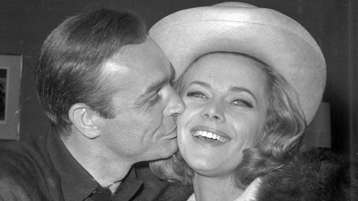 In this B/W file photo dated March 25, 1964, British actor Sean Connery kisses actress Honor Blackman during a party at Pinewood Film Studios, in Iver Heath, England. Blackman, the actor best-known for playing Bond girl Pussy Galore, hasdied of natural causes unrelated to coronavirus, aged 94, according to an announcement Monday April 6, 2020. (AP Photo, FILE)