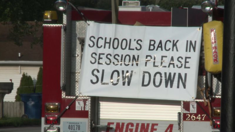 A sign asking drivers to slow down for students.