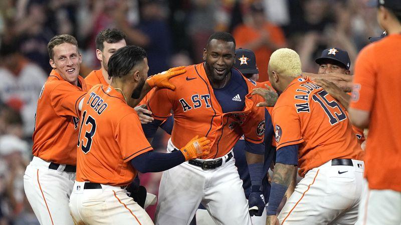 Houston Astros' Yordan Alvarez, center, celebrates with teammates after hitting a game-winning...