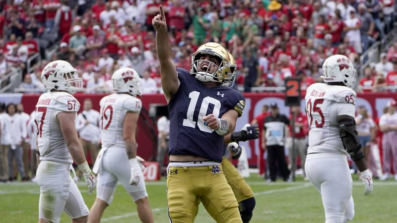 Notre Dame quarterback Drew Pyne celebrates his touchdown pass to wide receiver Kevin Austin...