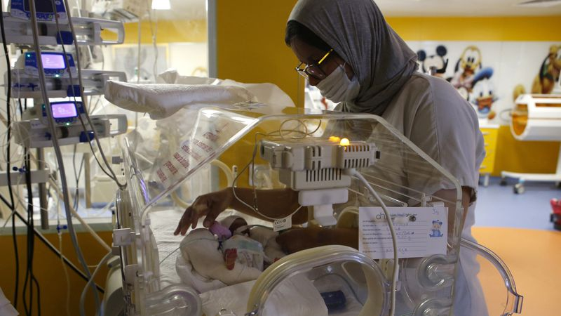 A Moroccan nurse takes care of one of the nine babies protected in an incubator at the...
