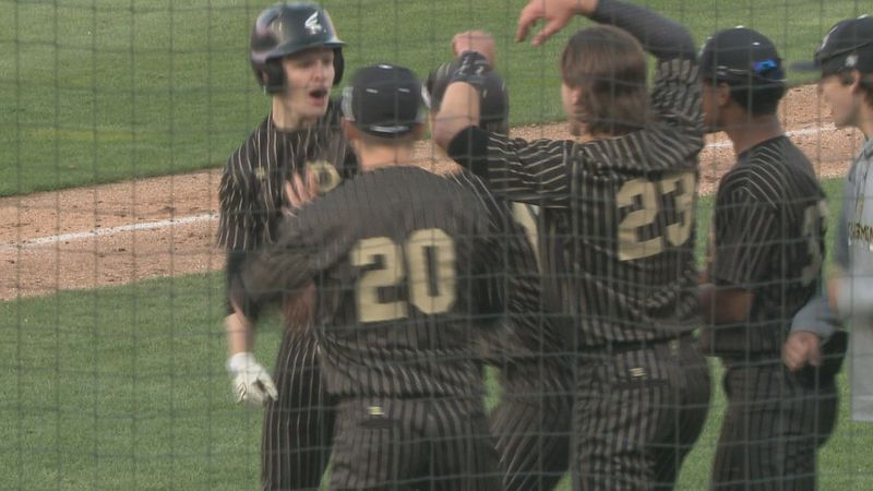Nate Kelly's teammates surround him after hitting a solo shot at Four Winds Field in a battle...