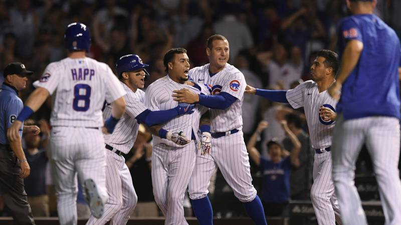 Chicago Cubs' Javier Baez center, celebrates with teammates after hitting a walk-off single in...