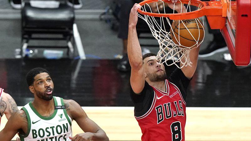Chicago Bulls guard Zach LaVine, right, dunks past Boston Celtics center Tristan Thompson...