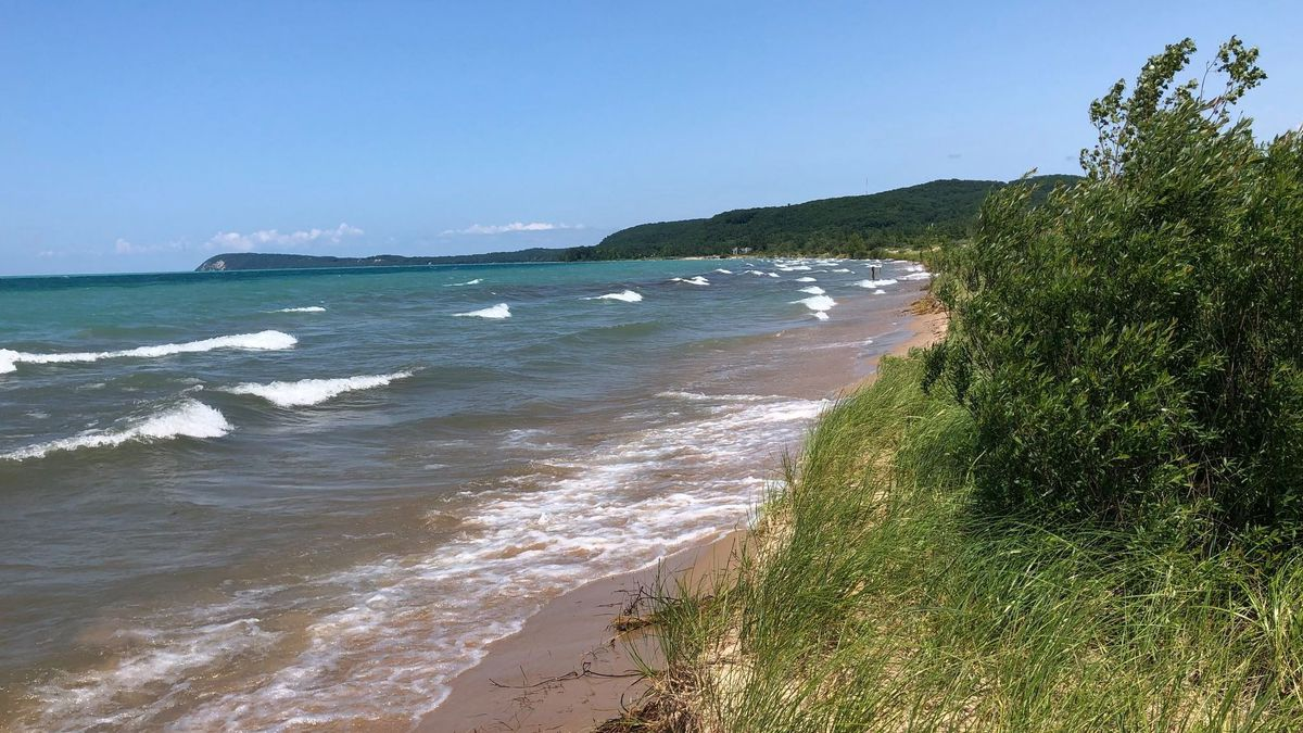 Waves crash onto the shore of Good Harbor Bay Beach under a blue sky with tree-covered hills in the background. (Photo from Sleeping Bear Dunes National Lakeshore)