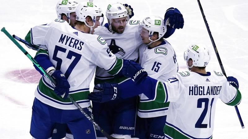 Vancouver Canucks center Jason Dickinson, center, celebrates with teammates after scoring...