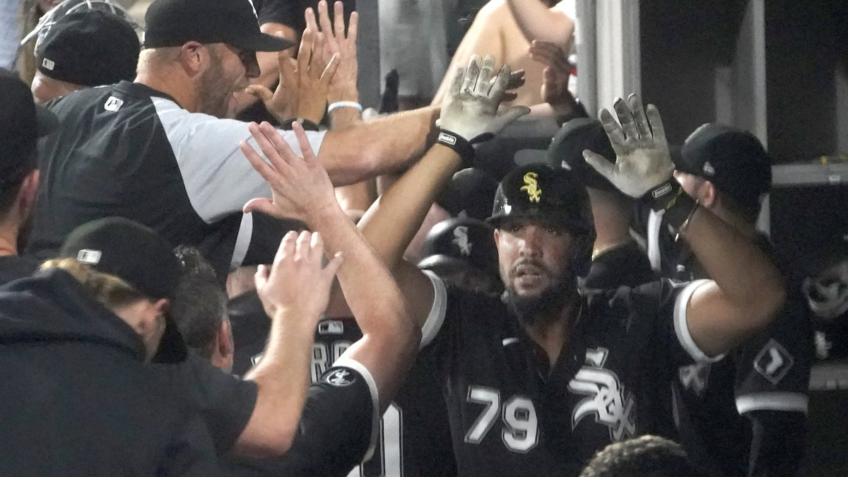 Chicago White Sox's Jose Abreu is congratulated in the dugout after his three-run home run...