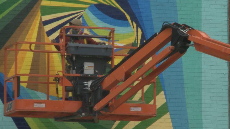 Alex Allen paints mural at Eddy Street Apartments.