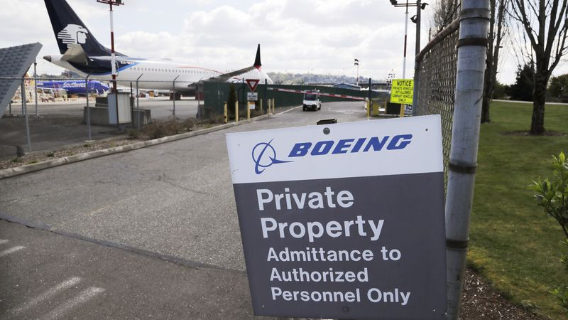 In this April 20, 2020, file photo, planes sit parked behind a sign marking Boeing property at...