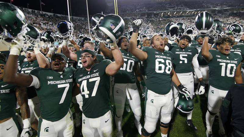 Michigan State players celebrate following their overtime win against Nebraska in an NCAA...