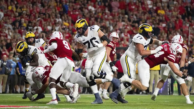 Michigan's Hassan Haskins, left, runs in for a touchdown against Nebraska linebacker Nick...