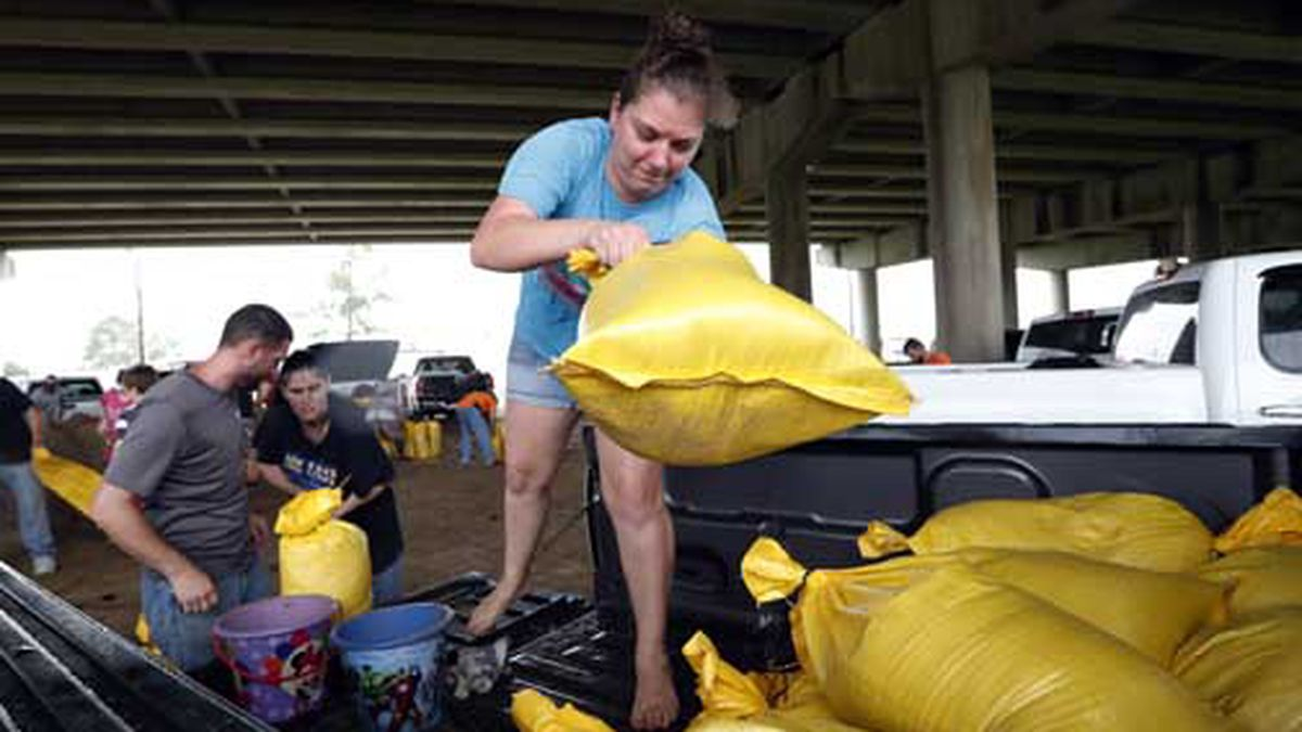 Tiffany Delee tosses a filled sandbag into the back of the family truck, while her husband Mike Delee, left, readies to tie up another bag, in Morgan City, La., Friday, July 12, 2019. The Delee's will use the bags to help protect their grandmother's house in the city. (AP Photo/Rogelio V. Solis)