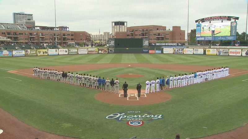 The South Bend Cubs and the Quad Cities River Bandits stand for the National Anthem ahead of...