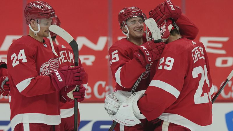 Detroit Red Wings goaltender Thomas Greiss (29) is greeted by forward Jakub Vrana (15) after...