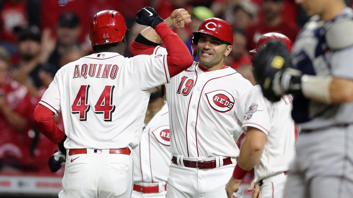 Cincinnati Reds' Aristides Aquino (44) bumps arms with Joey Votto (19) after Aquino crossing...