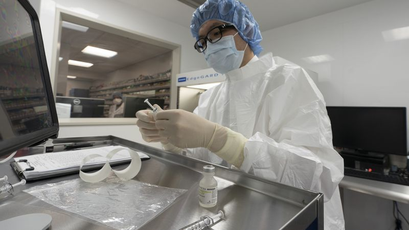 A pharmacist labels syringes in a clean room where doses of COVID-19 vaccines will be handled,...