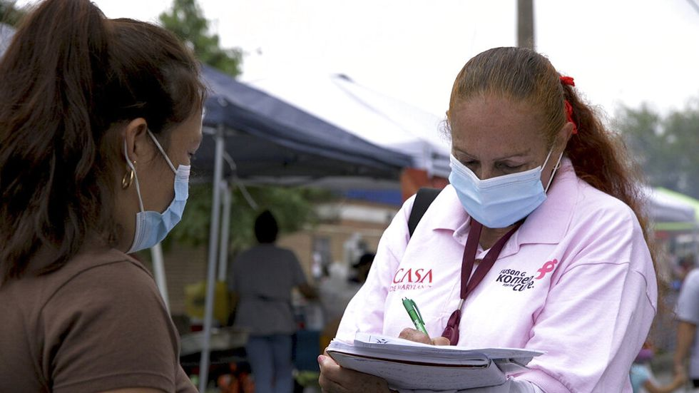 A 'promotora' (health promoter) from CASA, a Hispanic advocacy group, tries to enroll Latinos as volunteers to test a potential COVID-19 vaccine, at a farmers market in Takoma Park, Maryland on Sept. 9, 2020. Minority enrollment in studies of two shots has inched up in recent weeks, but even more is needed this fall as additional vaccine testing gets underway over the next two months.