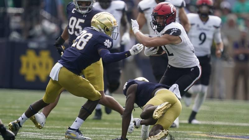 Cincinnati's Alec Pierce (12) is tackled by Notre Dame's TaRiq Bracy (28) and Cam Hart (5)...