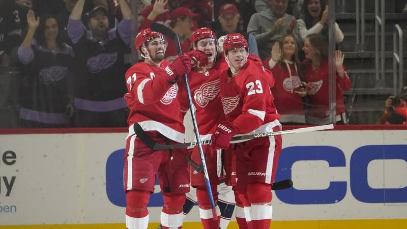 Detroit Red Wings left wing Tyler Bertuzzi, center, celebrates his goal with Dylan Larkin (71),...