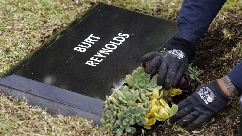 Flowers are placed in front of a temporary headstone for the late actor Burt Reynolds in the...