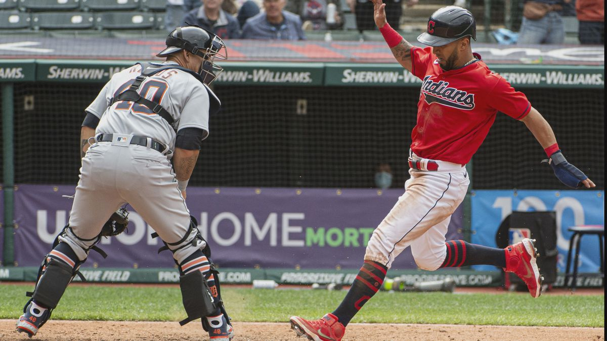 Cleveland Indians' Eddie Rosario, right, scores on a single by Franmil Reyes as Detroit Tigers'...