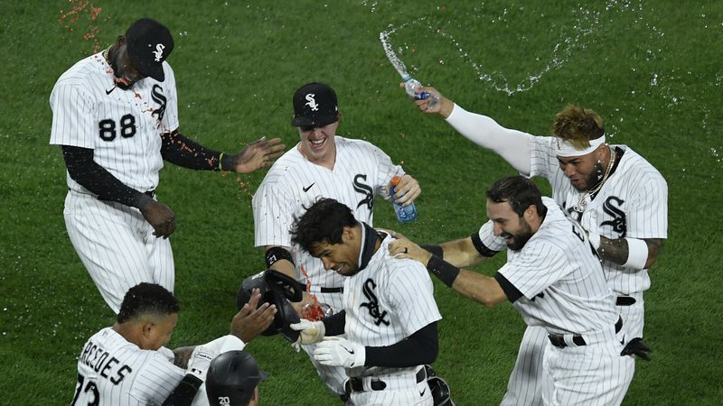 Chicago White Sox's Nick Williams, center, is mobbed by teammates after his fielder's choice...