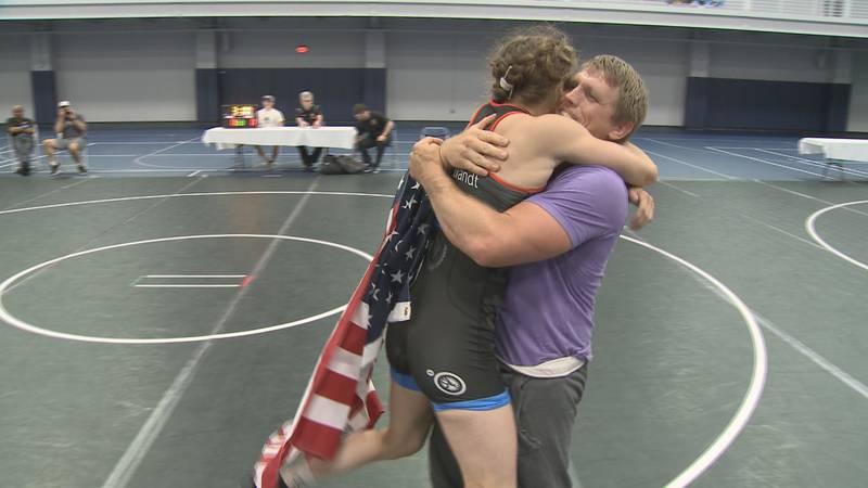 Sarah Hildebrandt hugs her coach Brad Harper at Saint Mary's College after winning a gold medal...