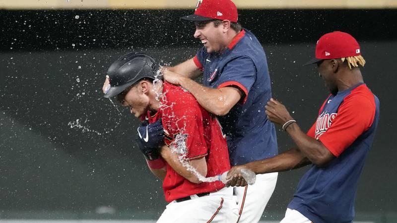 Minnesota Twins' Max Kepler, left, gets a water shower after his walk-off, bases-loaded single...