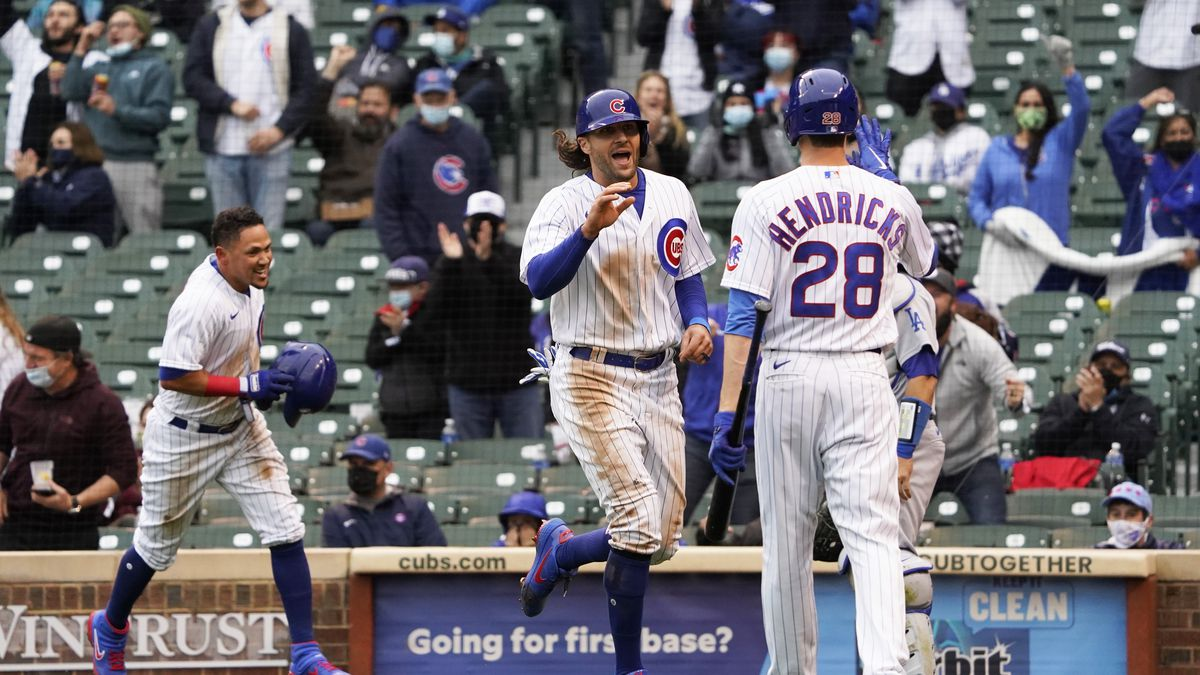 Chicago Cubs' Ildemaro Vargas, left and Jake Marisnick, center, celebrate after scoring on a...