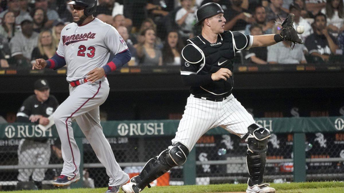 Minnesota Twins' Nelson Cruz (23) scores past Chicago White Sox catcher Zack Collins, off a...