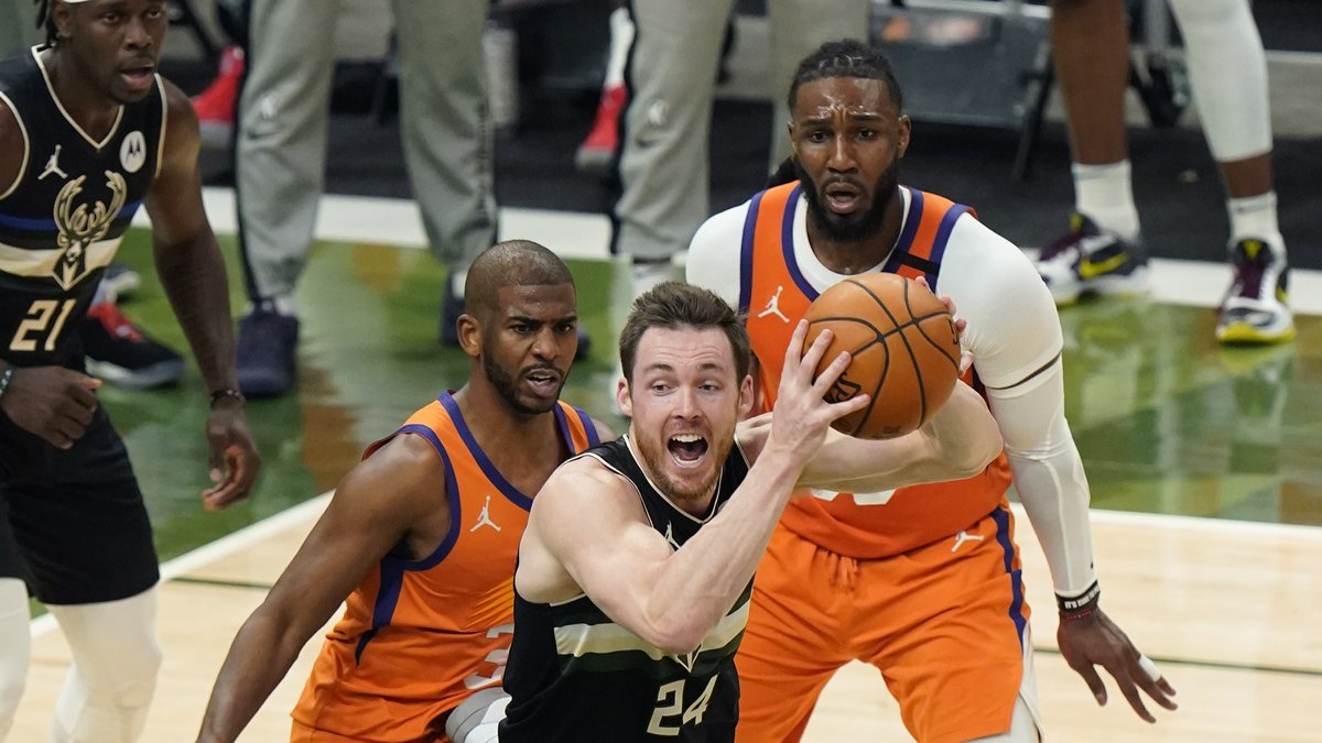 Milwaukee Bucks guard Pat Connaughton (24) looks to pass under pressure from Phoenix Suns guard...