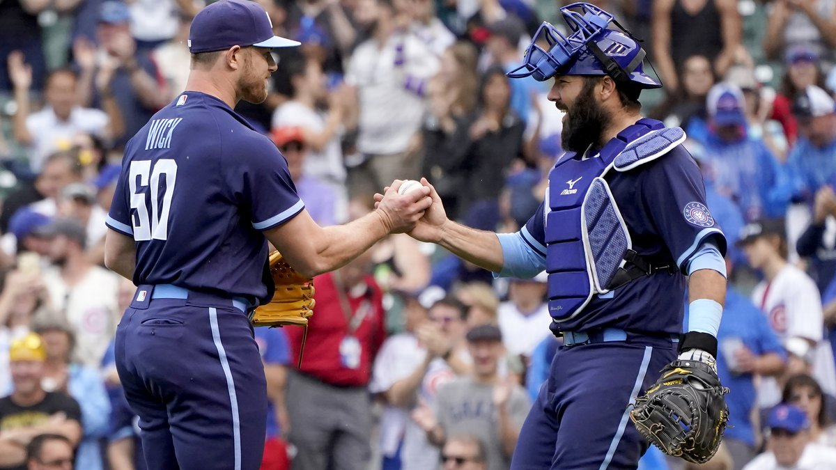 Chicago Cubs relief pitcher Rowan Wick, left, and catcher Austin Romine celebrate their win...