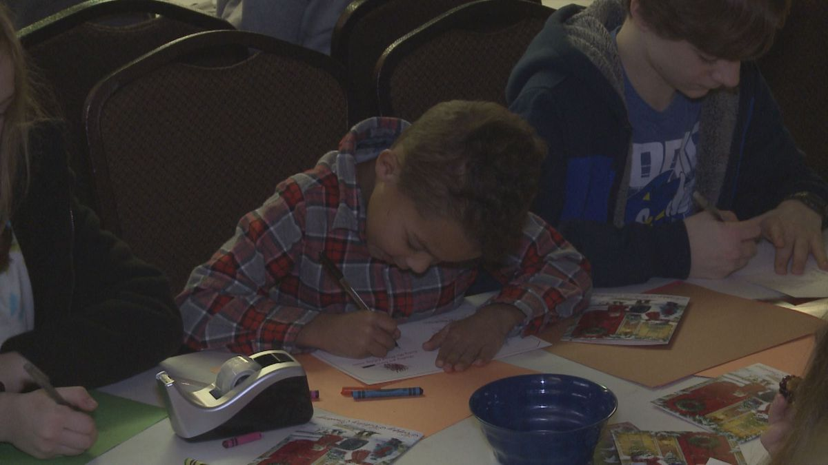 Young volunteers decorate Christmas cards to be sent to asylum seeking families that are being detained in the United States.
