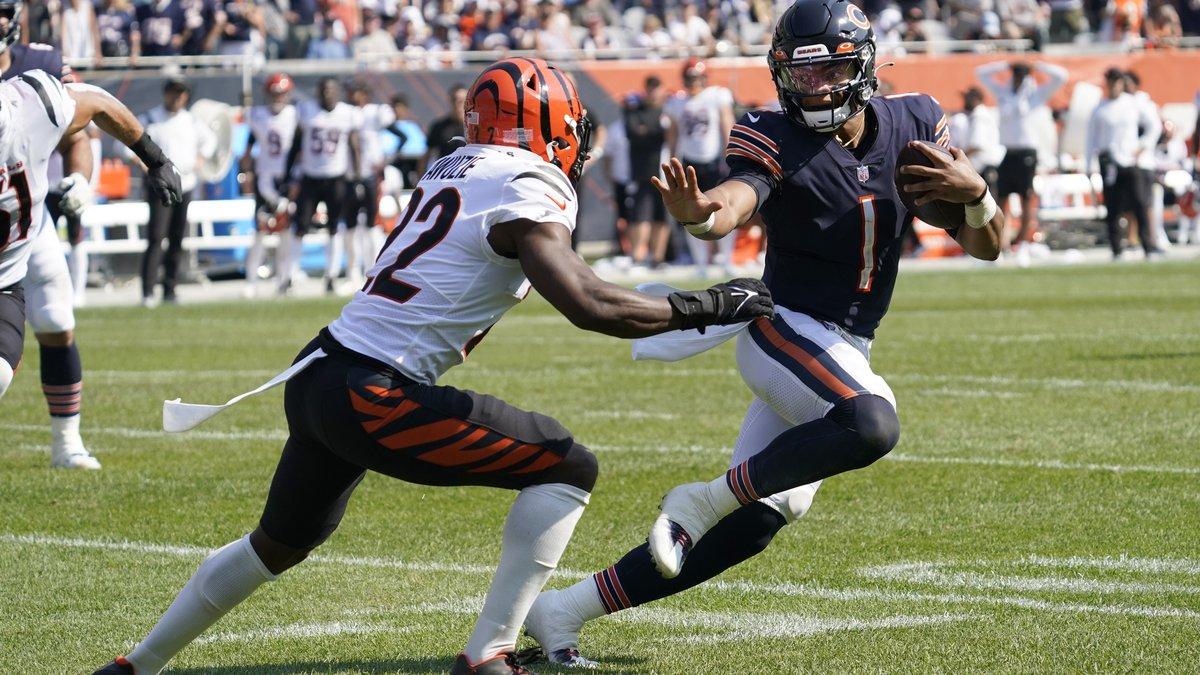Chicago Bears quarterback Justin Fields (1) prepares to stiff-arm Cincinnati Bengals cornerback...